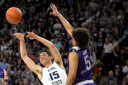 Abel Porter, Cody John. Utah State guard Abel Porter (15) passes the ball as Weber State guard Cody John (5) defends during the second half of an NCAA college basketball game, in Logan, Utah