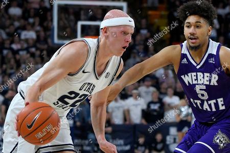 Brock Miller, Cody John. Utah State guard Brock Miller (22) is defended by Weber State guard Cody John (5) during the second half of an NCAA college basketball game, in Logan, Utah