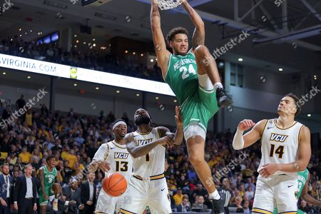North Texas' Zachary Simmons (24) hangs from the rim after dunking against VCU's Thomas Bell (13), Mike'L Simms (1) and Marcus Santos-Silva (14) during the second half of an NCAA college basketball game in Richmond, Va