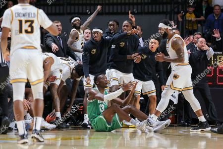 The VCU bench jumps up after a collision between North Texas' Thomas Bell, center, and VCU's Malik Crowfield, left, during the second half of an NCAA college basketball game in Richmond, Va