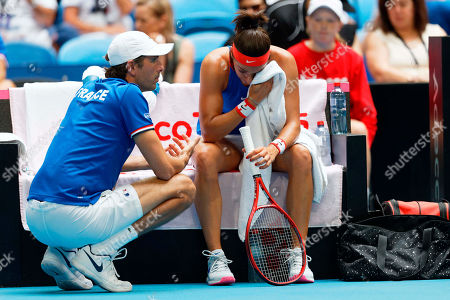 Julien Benneteau, Caroline Garcia. French Captain Julien Benneteau consoles Caroline Garcia as she suffered a defeat by Australia's Ashleigh Barty during their Fed Cup tennis final in Perth, Australia