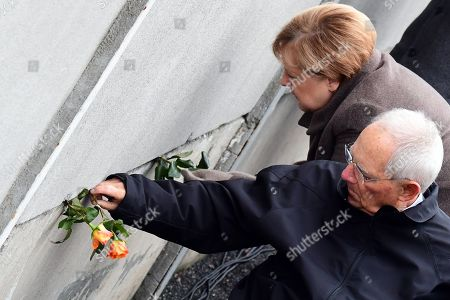 German Chancellor Angela Merkel (L) and the president of the German Parliament Bundestag Wolfgang Schaeuble (R) place a rose into a gap of the hinterland wall during the celebrations of the 30th anniversary of the fall of the Berlin Wall at the Berlin Wall Memorial site along Bernauer street in Berlin, Germany, 09 November 2019. The fall of the Berlin Wall led to the collapse of the communist East German GDR government in 1989 and the eventual reunification of East and West Germany.