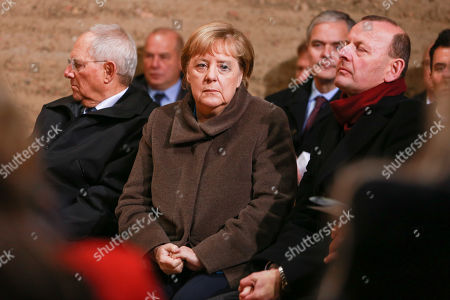 Stock Image of (L-R) President of the German Bundestag Wolfgang Schaeuble, German Chancellor Angela Merkel (C) and director of the Berlin Wall Memorial Axel Klausmeier attend a prayer in the Chapel of Reconciliation for the celebrations of the 30th anniversary of the fall of the Berlin Wall at the Berlin Wall Memorial site along Bernauer street in Berlin, Germany, 09 November 2019. The fall of the Berlin Wall led to the collapse of the communist East German GDR government in 1989 and the eventual reunification of East and West Germany.