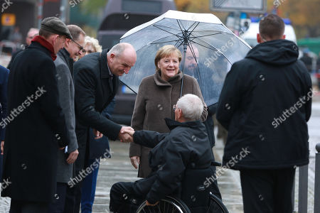 German Chancellor Angela Merkel (with umbrella) and President of the German Bundestag Wolfgang Schaeuble (sitting) arrive for the celebrations of the 30th anniversary of the fall of the Berlin Wall at the Berlin Wall Memorial site along Bernauer street in Berlin, Germany, 09 November 2019. The fall of the Berlin Wall led to the collapse of the communist East German GDR government in 1989 and the eventual reunification of East and West Germany.