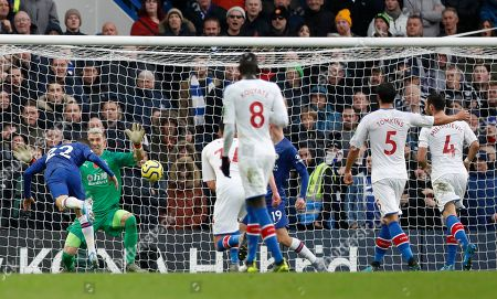 Chelsea's Christian Pulisic, left, scores his sides second goal past Crystal Palace's goalkeeper Vicente Guaita, 2nd left, during their English Premier League soccer match between Chelsea and Crystal Palace at Stamford Bridge stadium in London