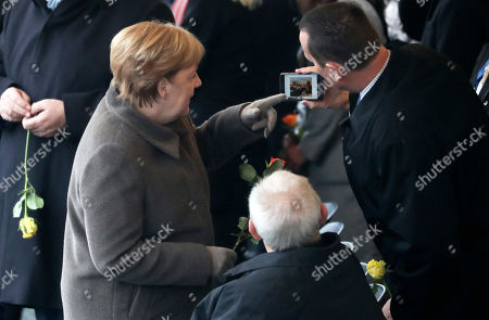 US Ambassador to Germany Richard Allen Grenell (R) shows German Chancellor Angela Merkel (L) and the president of the German Parliament Bundestag Wolfgang Schaeuble (C) a picture of a statue of former US President Ronald Reagan on his phone during the celebrations of the 30th anniversary of the fall of the Berlin Wall at the Berlin Wall Memorial site along Bernauer street in Berlin, Germany, 09 November 2019. The fall of the Berlin Wall led to the collapse of the communist East German GDR government in 1989 and the eventual reunification of East and West Germany.