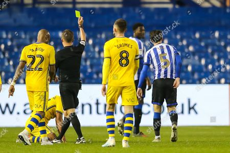 Sheffield Wednesday midfielder Kieran Lee (5) is shown a yellow card by the referee David Webb after a foul on Swansea City midfielder Wayne Routledge (15) during the EFL Sky Bet Championship match between Sheffield Wednesday and Swansea City at Hillsborough, Sheffield