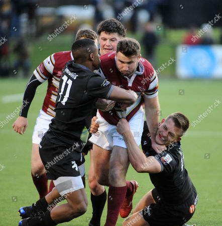 Stock Picture of Joe Reynolds - Watsonians centre powers through the tackles of Lindokuhle Mvelase-Julyan - Southern Knights winger and opposite number Thomas Galbraith.