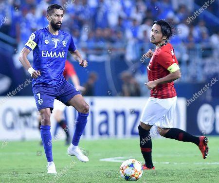 Al Hilal's Salman Al Faraj, left, plays the ball past Urawa Reds' Shinzoh Kohrogi during the AFC Champions League final soccer match between Al Hilal and Urawa Red at King Fahd stadium in Riyadh, Saudi Arabia