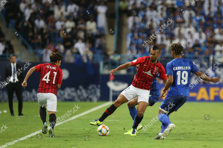 Stock Picture of Al-Hilal player Andre Carrillo (R) in action against Urawa Red Diamonds player FABRICIO (C) and Urawa Red Diamonds player Takahiro SEKENE  (L) during the AFC Champions League final First leg match between Al-Hilal and Urawa Red Diamonds at King Saud University Stadium, Al-Riyadh, Saudi Arabia, 09 November 2019.