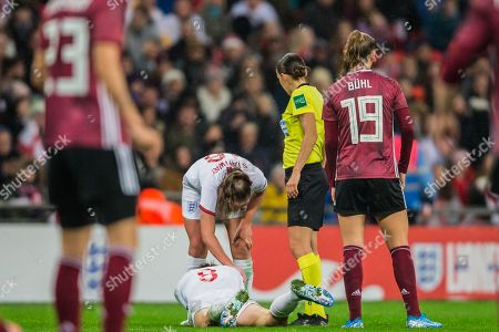 Jill Scott (England) injured following a tackle with Klara Buhl (Germany) with Georgia Stanway (England) checking how she is with Stephanie Frappart, Referee looking on during the International Friendly match between England Women and Germany Women at Wembley Stadium, London