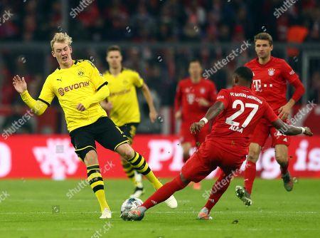 Dortmund's Julian Brandt, left, duels for the ball with Bayern's David Alaba during the German Bundesliga soccer match between FC Bayern Munich and Borussia Dortmund, in Munich, Germany