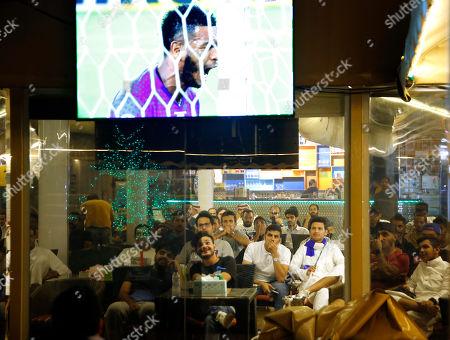 Saudi soccer fans watch the first leg of the AFC Champions League final soccer match between Al Hilal and Urawa Red at the Light Moon coffee shop in Jiddah, Saudi Arabia, . Al Hilal defender Ali Al-Bulaihi seen on the screen