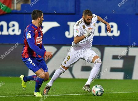 Real Madrid's Karim Benzema, right, duels for the ball with Eibar's Pedro Bigas during the Spanish La Liga soccer match between Eibar and Real Madrid at Ipurua stadium, in Eibar, northern Spain