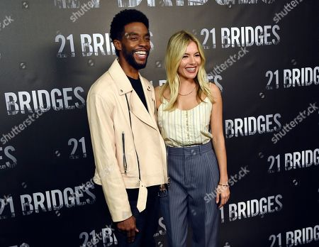 """Chadwick Boseman, Sienna Miller. Chadwick Boseman, left, and Sienna Miller, cast members in """"21 Bridges,"""" pose together during a photo call for the film at the Four Seasons Hotel, in Los Angeles"""
