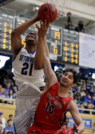 Seton Hall center Ike Obiagu (21) is fouled by Stony Brook guard Jordan Mckenzie (10) during the first half of an NCAA college basketball game, in South Orange, N.J