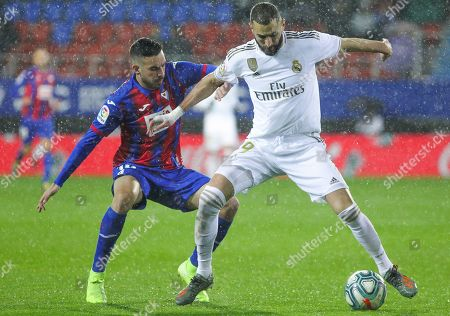 Karim Benzema, player of Real Madrid from France, and Edu Exposito, player of Eibar from Spain, fight for the ball