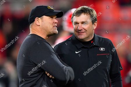 Missouri coach Barry Odom, left, and Georgia coach Kirby Smart talk on the field before an NCAA college football game, in Athens, Ga