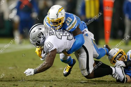 Stock Picture of Los Angeles Chargers defensive back Desmond King II (20) tackles Oakland Raiders running back Jalen Richard (30) during an NFL football game in Oakland, Calif