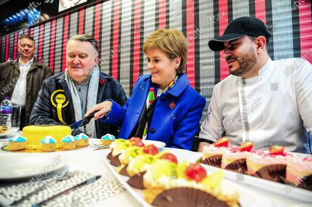 Keith Brown, John Nicolson, First Minister Nicola Sturgeon and Muhanad Alwen of Alwen Cakes cut an SNP decorated cake during John Nicolson's election campaign ahead of the 2019 General Election.