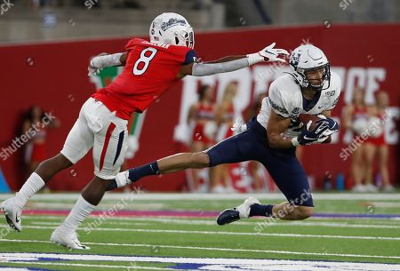 Utah State tight end Caleb Repp catches a pass as Fresno State safety Chris Coleman defends during the first half of an NCAA college football game in Fresno, Calif
