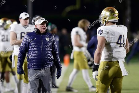 Notre Dame head coach Brian Kelly speaks with Notre Dame defensive lineman Kurt Hinish (41) during the first half of an NCAA college football game against Duke in Durham, N.C
