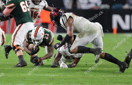 Miami Hurricanes running back Cam'Ron Harris (23) advances the ball tackled by Louisville Cardinals linebacker Dorian Etheridge (17) during a college football game at the Hard Rock Stadium in Miami Gardens, Florida. The Hurricanes won 52-27
