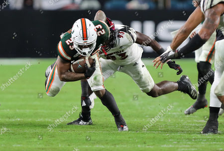 Miami Hurricanes running back Cam'Ron Harris (23) advances the ball pressured by Louisville Cardinals defensive lineman Gary McCrae (93) during a college football game at the Hard Rock Stadium in Miami Gardens, Florida. The Hurricanes won 52-27