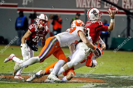 Stock Photo of North Carolina State quarterback Devin Leary (13) gets hit by Clemson's Chad Smith (43) and Lannden Zanders (36) with State's Jordan Houston (20) nearby during the second half of an NCAA college football game in Raleigh, N.C
