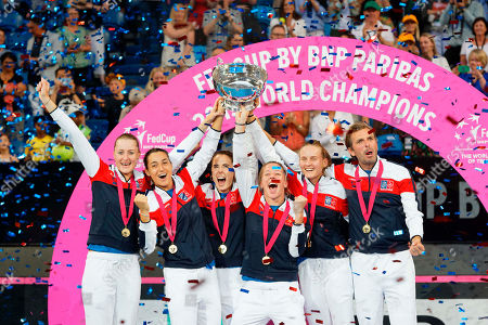 French team, from left, Kristina Mladenovic, Caroline Garcia, Alize Cornet, Pauline Parmentier, Fiona Ferro and captain Julien Benneteau celebrate on the podium after defeating Australia to win the Fed Cup tennis final in Perth, Australia