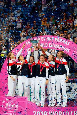 Stock Photo of French team, from left, Kristina Mladenovic, Caroline Garcia, Alize Cornet, Pauline Parmentier, Fiona Ferro and cCaptain Julien Benneteau celebrate on the podium after defeating Australia to win the Fed Cup tennis final in Perth, Australia