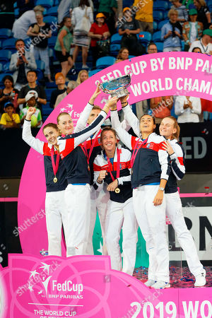 French team, from left, Alize Cornet, Kristina Mladenovic, captain Julien Benneteau, Pauline Parmentier, Caroline Garcia and Fiona Ferro celebrate on the podium after defeating Australia to win the Fed Cup tennis final in Perth, Australia
