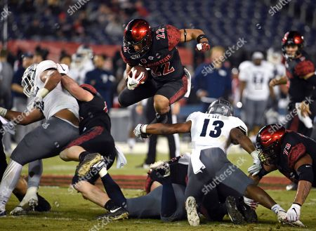 San Diego State running back Chase Jasmin (22) jumps over Nevada defensive back Jordan Lee (13) during the first half of a college football game, in San Diego. U.S