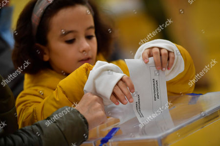 Stock Photo of A young girl casts the vote of a relative for the general election in Pamplona, northern Spain,. Spaniards were voting Sunday in the country's fourth election in as many years with Catalonia's secession drive and the predicted rise of a far-right party dominating the campaign