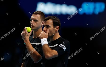 Stock Photo of Ivan Dodig of Croatia, right, and Filip Polasek of Slovakia talks before serving to Lukasz Kubot of Poland and Marcelo Melo of Brazil during their ATP World Tour Finals doubles tennis match at the O2 Arena in London