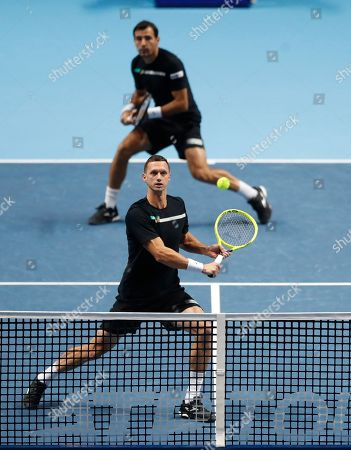 Ivan Dodig of Croatia, at rear, and Filip Polasek of Slovakia play a return to Lukasz Kubot of Poland and Marcelo Melo of Brazil during their ATP World Tour Finals doubles tennis match at the O2 Arena in London