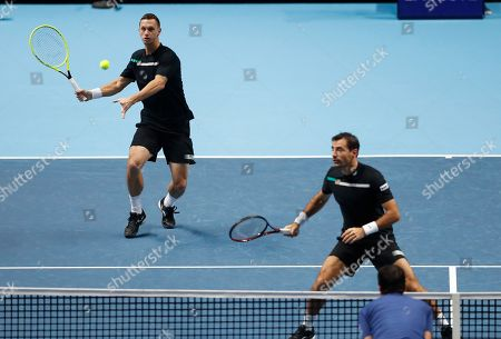 Ivan Dodig of Croatia, right, and Filip Polasek of Slovakia play a return to Lukasz Kubot of Poland and Marcelo Melo of Brazil during their ATP World Tour Finals doubles tennis match at the O2 Arena in London