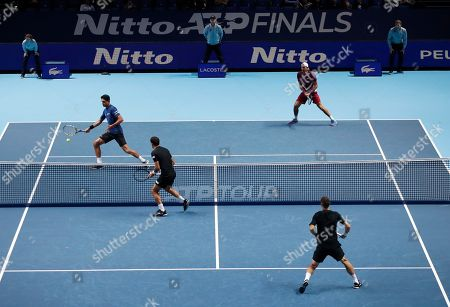 Lukasz Kubot of Poland, top right, and Marcelo Melo of Brazil play a return to Ivan Dodig of Croatia and Filip Polasek of Slovakia during their ATP World Tour Finals doubles tennis match at the O2 Arena in London