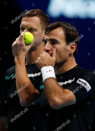 Ivan Dodig of Croatia, right, and Filip Polasek of Slovakia talks before serving to Lukasz Kubot of Poland and Marcelo Melo of Brazil during their ATP World Tour Finals doubles tennis match at the O2 Arena in London