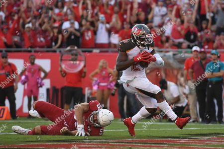 Tampa Bay Buccaneers running back Peyton Barber (25) beats Arizona Cardinals linebacker Joe Walker (59) on a 1-yard touchdown run during the second half of an NFL football game, in Tampa, Fla
