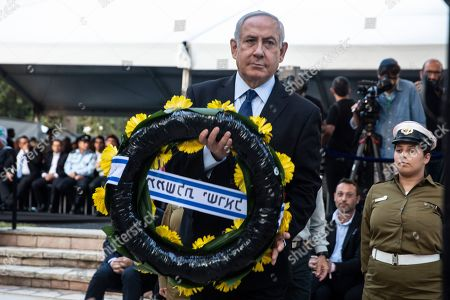 Israeli Prime Minister Benjamin Netanyahu holds a wreath as he stands before the grave of the late Yitzhak Rabin, during a state memorial ceremony for Yitzhak and Leah Rabin, at Mt. Herzl in Jerusalem, 10 November 2019. Yitzhak Rabin was shot dead on 04 November 1995 just two years after the signing of the Oslo peace accords, for which he and former Israeli president Shimon Peres were awarded the Nobel Peace Prize along with late veteran Palestinian leader Yasser Arafat.