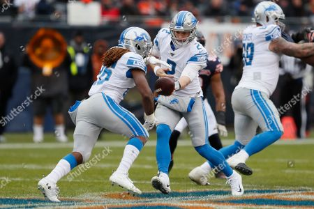Detroit Lions quarterback Jeff Driskel (2) hands off to Detroit Lions running back Paul Perkins (26) during the first half of an NFL football game against the Chicago Bears in Chicago