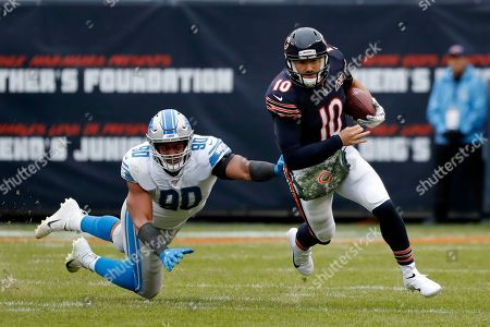 Chicago Bears quarterback Mitchell Trubisky (10) avoids a tackle byf Detroit Lions defensive end Trey Flowers (90) during the second half of an NFL football game in Chicago