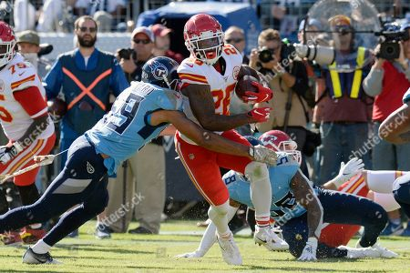 Kansas City Chiefs running back Damien Williams (26) is hit by Tennessee Titans inside linebacker Wesley Woodyard (59) in the first half of an NFL football game, in Nashville, Tenn