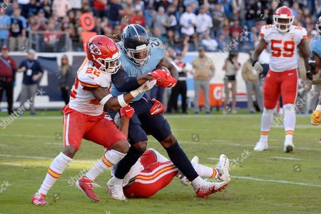 Tennessee Titans running back Derrick Henry pushes against Kansas City Chiefs free safety Juan Thornhill, left, in the second half of an NFL football game, in Nashville, Tenn