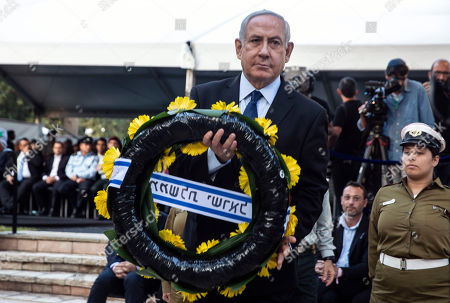 Israeli Prime Minister Benjamin Netanyahu holds a wreath atthe grave of the late Yitzhak Rabin at an official memorial for the former Israeli Prime Minister and his wife Leah, commemorating 24 years since the assassination of Rabin, at Mt. Herzl in Jerusalem