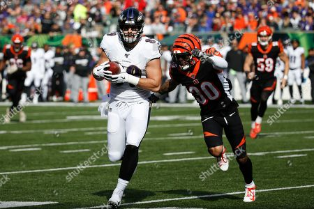 Stock Picture of Mark Andrews, Jessie Bates. Baltimore Ravens tight end Mark Andrews (89) runs the ball against Cincinnati Bengals free safety Jessie Bates (30) during the first half of NFL football game, in Cincinnati