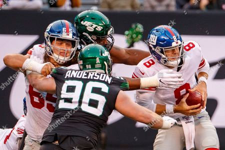 , 2019, New York Jets defensive end Henry Anderson (96) and outside linebacker Jordan Jenkins (48) reach for New York Giants quarterback Daniel Jones (8) as offensive guard Nick Gates (65) tries to block Anderson during the NFL game between the New York Giants and the New York Jets at MetLife Stadium in East Rutherford, New Jersey
