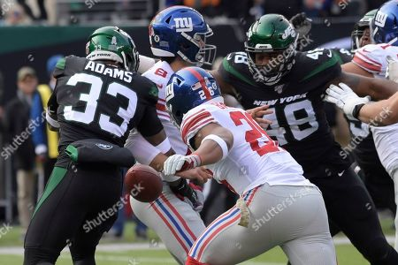 New York Jets strong safety Jamal Adams (33) knocks the ball away from New York Giants quarterback Daniel Jones (8) as Saquon Barkley (26) runs to recover the ball during the first half of an NFL football game, in East Rutherford, N.J