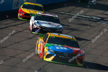 Kyle Busch (18) leads Denny Hamlin (11) and Joey Logano (22) into Turn 1 during a NASCAR Cup Series auto race at ISM Raceway, in Avondale, Ariz